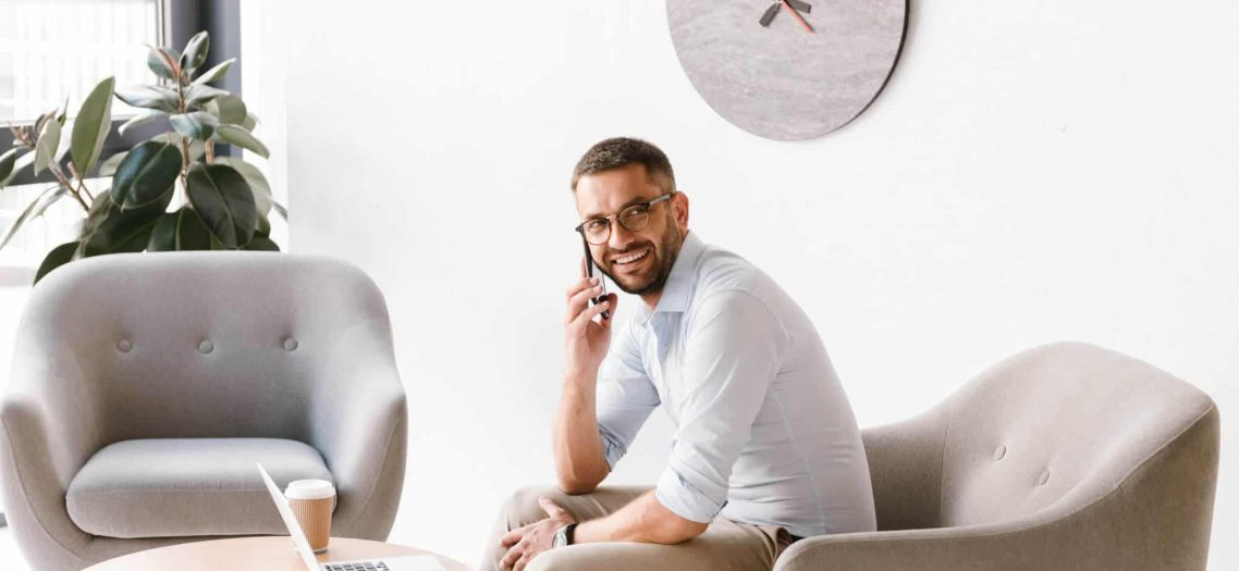 Photo of business man wearing stylish formal clothing sitting in armchair and working on laptop in office interior while talking on mobile phone