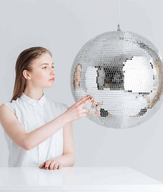 Woman sitting at the table with mirror ball